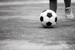 Petit garçon jouant le football dans la campagne Photos stock
