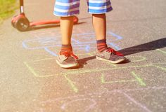 Petit garçon jouant le jeu de marelle sur le terrain de jeu Photo libre de droits