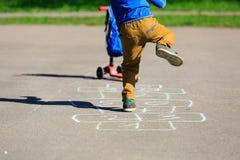 Petit garçon jouant le jeu de marelle sur le terrain de jeu Image stock