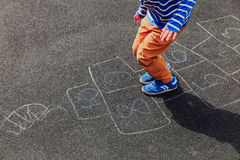 Petit garçon jouant le jeu de marelle sur le terrain de jeu Images libres de droits
