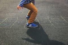 Petit garçon jouant le jeu de marelle sur le terrain de jeu Photos libres de droits