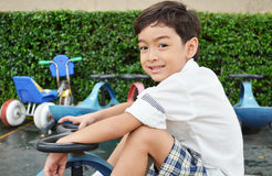 Petit garçon jouant le mini tricycle de voiture Photographie stock libre de droits