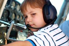 Petit garçon jouant le pilote dans l'avion Images stock
