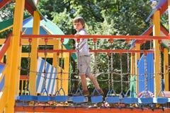 Petit garçon jouant sur la cour de jeu photo stock