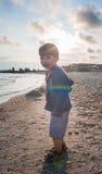 Petit garçon jouant sur le bord de la mer Photos stock