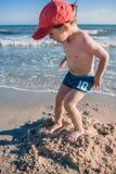 Petit garçon jouant sur le bord de la mer Image stock