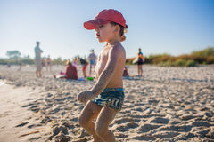 Petit garçon jouant sur le bord de la mer Image libre de droits
