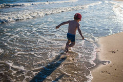 Petit garçon jouant sur le bord de la mer Images libres de droits