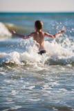 Petit garçon jouant sur le bord de la mer Photographie stock