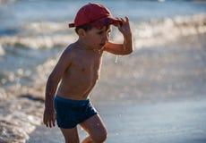 Petit garçon jouant sur le bord de la mer Images stock