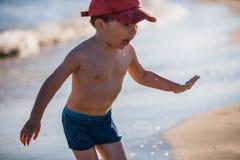 Petit garçon jouant sur le bord de la mer Photos libres de droits