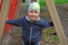 Petit garçon jouant sur le terrain de jeu en parc extérieur d'automne photographie stock libre de droits