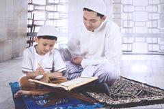 Petit garçon lisant le Quran avec son père Photos stock
