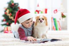 Petit garçon lisant un livre et un chien à Noël Images stock