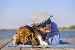 Petit garçon lyiing avec son chien par la rivière Photographie stock libre de droits