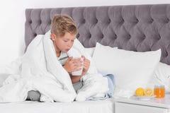 Petit garçon malade avec la tasse de thé chaud pour la toux images libres de droits