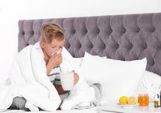 Petit garçon malade avec la tasse de thé chaud pour la toux photo libre de droits