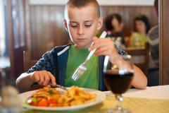 Petit garçon mangeant dans un restaurant Photo libre de droits