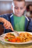 Petit garçon mangeant dans un restaurant Image libre de droits