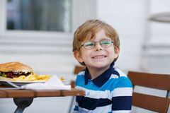Petit garçon mangeant des aliments de préparation rapide : pommes frites et hamburger Photographie stock