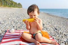 Petit garçon mangeant l'épi de maïs sur le bord de la mer Photographie stock libre de droits