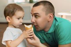 Petit garçon mangeant la crème glacée à la société de son père Photographie stock