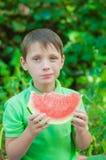 Petit garçon mangeant la pastèque pendant l'été Photographie stock