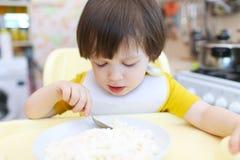 Petit garçon mangeant le quark avec la crème sure sur la cuisine Photo libre de droits