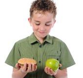 Petit garçon mangeant un hamburger Photographie stock