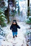 Petit garçon marchant dans la forêt d'hiver photos stock