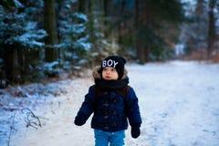 Petit garçon marchant dans la forêt d'hiver images stock