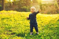 Petit garçon marchant en parc au printemps sur le coucher du soleil Photos libres de droits