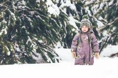 Petit garçon marchant en parc couvert de neige Photographie stock libre de droits