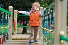 Petit garçon marchant sur les conseils sur le terrain de jeu Photographie stock