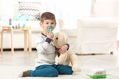 Petit garçon mignon à l'aide du nébuliseur à la maison photographie stock libre de droits