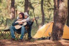 petit garçon mignon étreignant le père jouant la guitare photographie stock