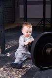Petit garçon mignon avec des haltères dans le gymnase convenable de croix Photo stock
