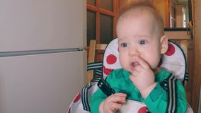 Petit garçon mignon avec deux dents inférieures mangeant des pailles et semblant conçu au côté se reposant dans la cuisine dans banque de vidéos