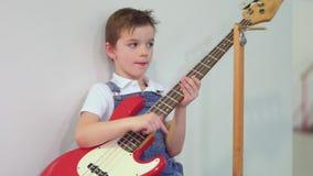 Petit garçon mignon avec la guitare électronique