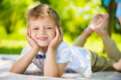Petit garçon mignon avec le papillon se trouvant sur l'herbe verte images stock