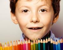 Petit garçon mignon avec le sourire haut étroit de crayons de couleur, visage d'éducation coloré Image stock