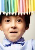 Petit garçon mignon avec le sourire haut étroit de crayons de couleur, visage d'éducation coloré Photos stock