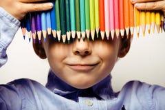 Petit garçon mignon avec le sourire haut étroit de crayons de couleur, visage d'éducation coloré Photo stock