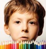 Petit garçon mignon avec le sourire haut étroit de crayons de couleur, visage d'éducation coloré Images stock