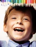 Petit garçon mignon avec le sourire haut étroit de crayons de couleur, visage d'éducation coloré Images libres de droits