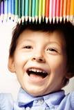 Petit garçon mignon avec le sourire haut étroit de crayons de couleur, visage d'éducation coloré Photographie stock libre de droits