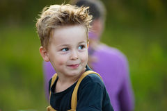 Petit garçon mignon avec les cheveux ébouriffés regardant de côté et souriant Photographie stock libre de droits
