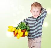 Petit garçon mignon avec les tulipes et le cadeau jaunes Images stock