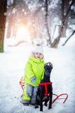 Petit garçon mignon avec ses amis de chien noir dans la forêt d'hiver Photo stock