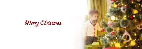 Petit garçon mignon décorant l'arbre de Noël avec l'espace blanc pour le texte photo libre de droits